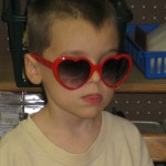 Little boy with heart glasses, compliments a friend during the Young Masters Little Wisdom Discovery Curriculum