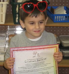 Young boy with Young Masters Little Wisdom Discovery certificate