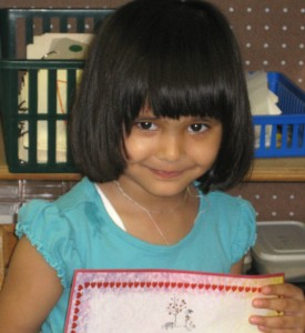 Little girl graduates from Young Masters LIttle Wisdom Discovery Program for Montessori